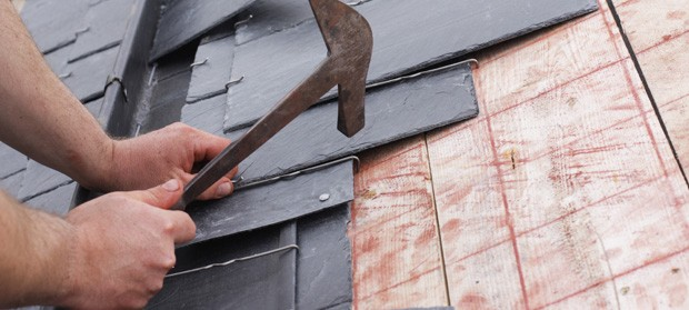 Roofer laying slate tiles